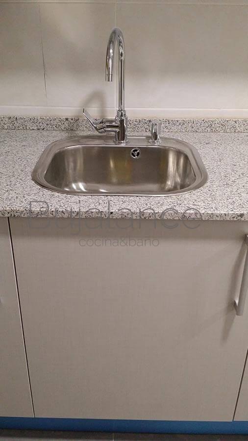 Mueble fregadero una puerta con poza sobre encimera sin escurridor y con aplicador de jabón.