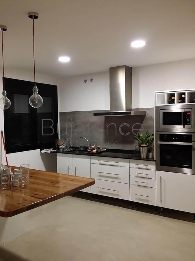 Cocina moderna en Graus con puertas en color blanco, granito repujado en mate y frontal en porcelánico de gran formato.