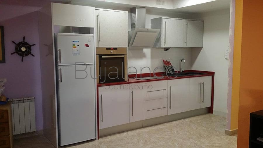 Cocina en color blanco con encimera Silestone rojo, el cliente quiso aprovechar la nevera de la anterior cocina.