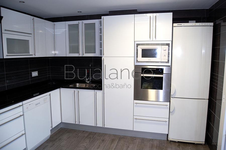 Lateral de cocina con columna de horno y microondas y al lado la nevera