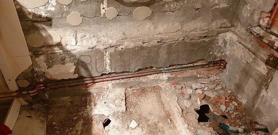 Al quitar la bañera se descubre una zona bastante inestable y con los tubos de calefacción por dentro