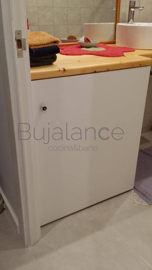 Mueble de lavadora oculta en reforma de baño antiguo en Graus