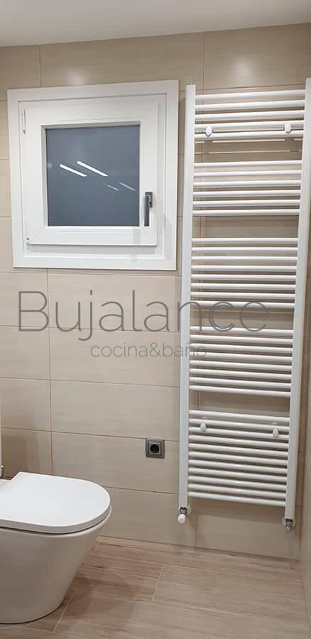 Zona de sanitario compacto de diseño y toallero lacado en blanco en reforma de baño moderna en Benasque